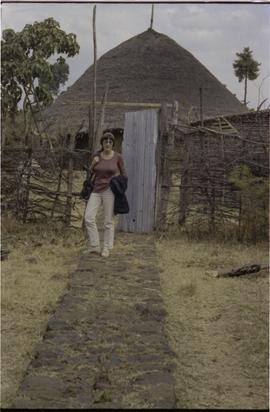 Lorna R. Marsden and a straw or mud  hut