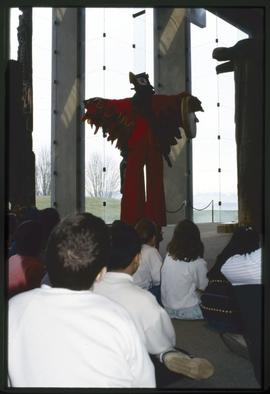 Children watch a performer in a bird costume
