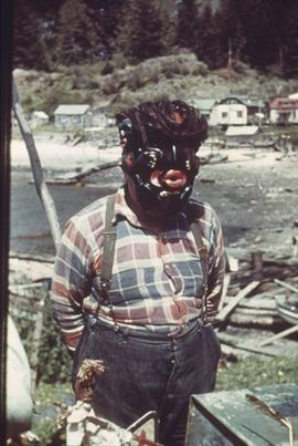Man in mask, near village and shoreline