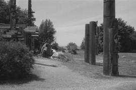 [View of canoe log and totem poles]