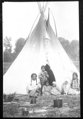 Portrait of man, woman, and children in front of tipi