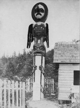 Totem pole at end of small building