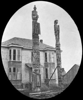 Two totem poles in front of two-story house