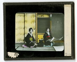 Two women kneeling in front of screens