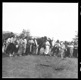 Group shot of individuals standing outside with horses