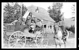 Group portrait of women and children on a wagon and boy on a horse