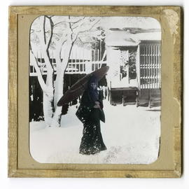 Woman holding parasol outside in snow