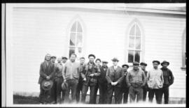 Group portrait of men posed beside a church