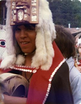Participant in button blanket, headdress, and with drum