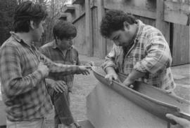 [Chip, Norman and Ron inspect and discuss model canoe]