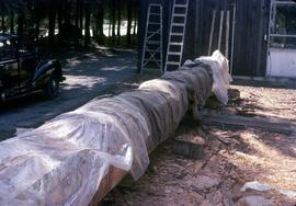 Partially carved totem pole draped in tarps