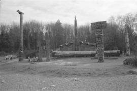 [Canoe log, totem poles, and long house]
