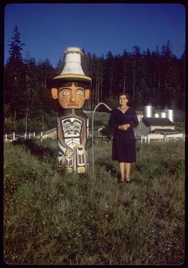Woman next to short totem pole