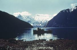 Fishing boat on water with snow covered mountains in background