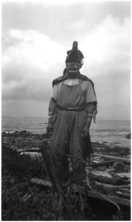 Man on beach wearing headdress and robe