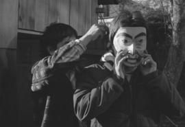 [Norman Tait assists unidentified person with mask]