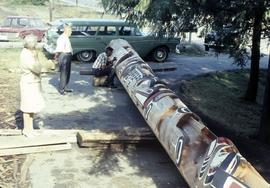 Carving a partially finished totem pole
