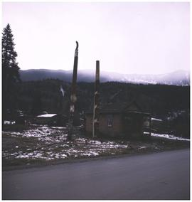 Totem poles, house, and mountains