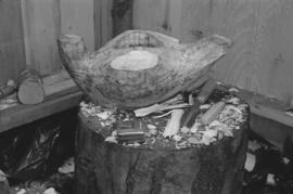 [Tree stump with carving and tools]