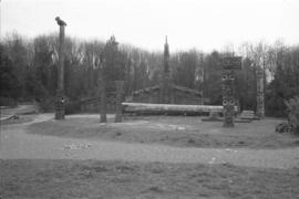 [Wide shot of MOA grounds, Mortuary House, totems and canoe log]