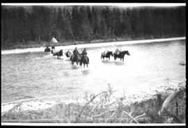 Men on horseback crossing a river