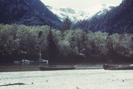 Canoes on shore and boats in river, near mountains