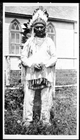 Portrait of a man in native clothing  standing near a church