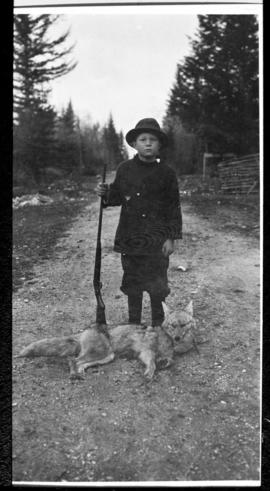 Portrait of a boy, rifle, and dog