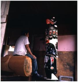 Sam Johnson, carver, with one of his totem poles, Gwayasdums