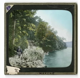Man standing beside stone stairs along river