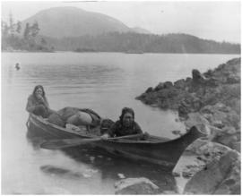 [Two women in canoe carrying goods]