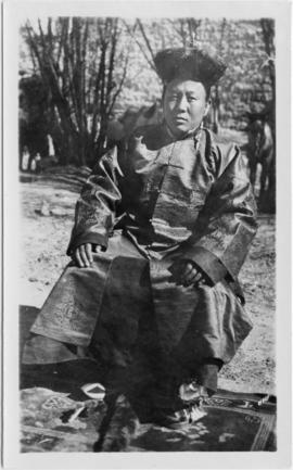 "Tibetian man seated outdoors; identified in notes as ""Shasw Khusho."" Woman in a033681 i..."