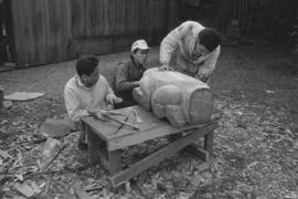 [Chip, Isaac, and Ron continue shaping large beaver bowl carving]