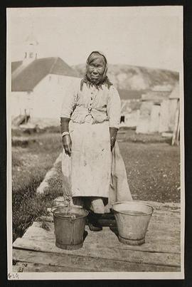 Woman Standing with Two Buckets at her Feet