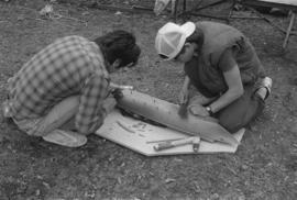 [Making adjustments to underside of model canoe]