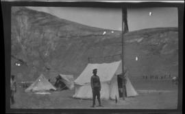 Tibetan soldier standing in front of an army tent