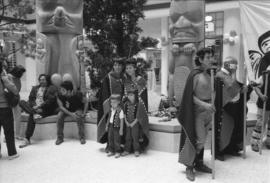 [Isaac Tait with unidentified persons in front of totems]