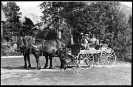 Portrait of man, woman, and two children in a horse-drawn wagon