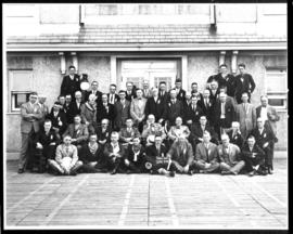 Group portrait of men in front of large building, view two