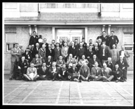 Group portrait of men in front of large building