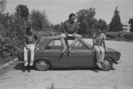 [Isaac, Ron, and Chip sit on top of car]