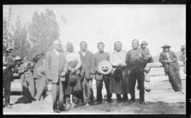 Group portrait of men posed along a split rail fence