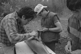 [Chip, Isaac and Norman adjusting model canoe]