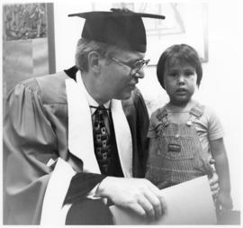 [Bill Reid in graduation gown with a child]