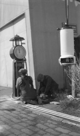 Two men installing a gasoline pump