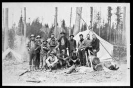 Group portrait of twelve men standing in front of a tent