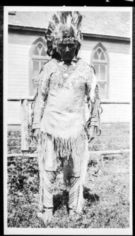 Portrait of a man in native dress  standing near a church