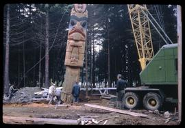 Bill Reid watching memorial pole being raised in the Haida Village