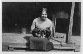 Photo of a seated woman holding four puppies
