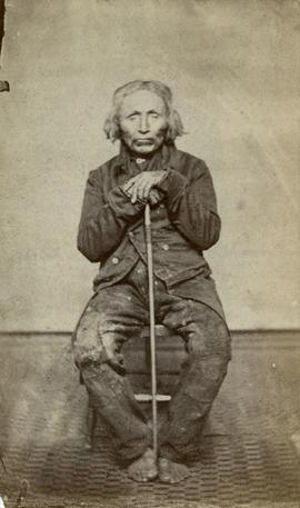 [Portrait of man seated with cane]